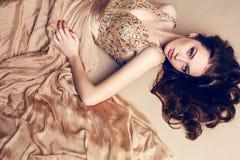 Härlig brunett i den lyxiga paljettklänningen som poserar på studion Royaltyfri Bild