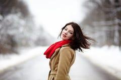Härlig brunett med hår som blåsas av vind i vintern Arkivfoton