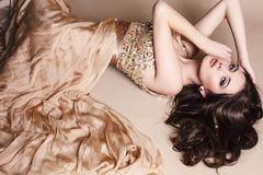 Härlig brunett som bär den lyxiga beigea klänningen Royaltyfri Bild