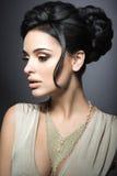 Härlig brunettkvinna med perfekt hud, guld- makeup och handgjorda smycken Härlig le flicka Arkivbilder