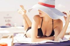 Härlig brunettkvinna på stranden i pöl bara som in kopplar av Arkivbild