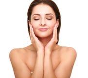 Härlig brunnsortkvinna med ren skönhethud som trycker på hennes framsida Royaltyfria Bilder