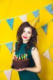 Härlig caucasian flicka som blåser stearinljus på henne kaka Beröm och parti Arkivfoto