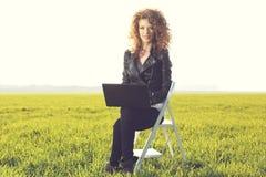 Härlig dam med hennes bärbar dator på gräs Royaltyfri Fotografi