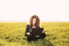 Härlig dam med hennes bärbar dator på gräs Arkivfoton