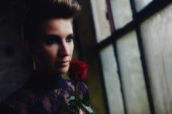 Härlig elegant dam som rymmer den röda rosen Fotografering för Bildbyråer