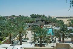 Härlig fantastisk sikt av simbassängen som omges av palmträd på den lyxiga arabiska ökensemesterorten Arkivbild