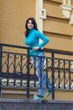 Härlig flicka i en blå halvpolokrage nära räcket Royaltyfria Bilder