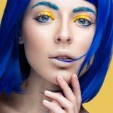 Härlig flicka i en ljus blå peruk i stilen av cosplay och idérik makeup Härlig le flicka Långt exponeringsfoto som tas i en tunne Royaltyfria Foton