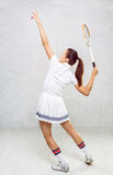 Härlig flicka i tenniskläder som svänger på en tennisracket Royaltyfri Fotografi