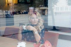 Härlig flicka inom ett kafé med koppen kaffe Arkivbilder