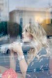 Härlig flicka inom ett kafé med koppen kaffe Arkivfoto