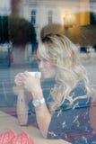 Härlig flicka inom ett kafé med koppen kaffe Fotografering för Bildbyråer