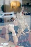 Härlig flicka inom ett kafé med koppen kaffe Arkivfoton
