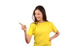 Härlig flicka med den gula t-skjortan som pekar till sidan. Royaltyfria Bilder