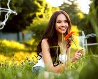Härlig flicka med den röda blomman. Härlig modell Woman Face. Arkivbilder