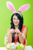 Härlig flicka med en korg av påskägg I Arkivbild