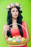 Härlig flicka med en korg av påskägg I Arkivfoto