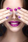 Härlig flicka med ett ljust aftonsmink och lilamanikyr med bergkristaller Spika designen Härlig le flicka Royaltyfri Bild
