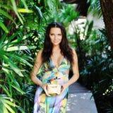 Härlig flicka med kokosnötcoctailen i tropisk trädgård Arkivbilder