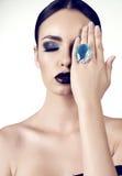 Härlig flicka med mörkt hår med ljus överdådig makeup och smycket Royaltyfri Fotografi
