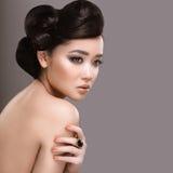 Härlig flicka med orientaliskt typaftonhår och makeup Härlig le flicka Royaltyfria Foton