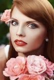 Härlig flicka med rosa rosor i hennes hår Arkivfoto