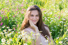 Härlig flicka på gläntan med ängblommor Arkivfoto