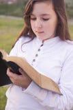 Härlig flicka som läser den heliga bibeln Arkivbilder