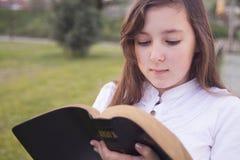 Härlig flicka som läser den heliga bibeln Arkivbild