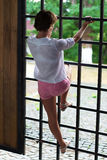 Härlig flickaklättring på en järnstång i en gammal välvd walkwa Arkivfoton
