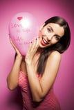 Härlig gladlynt kvinna med valentindagballongen Arkivfoto