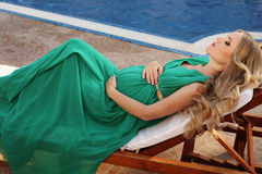 Härlig gravid kvinna med blont hår i elegant klänning Arkivfoton