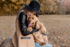 Härlig gullig lycklig flicka i en svart hatt som spelar med hennes hund i en parkera Fotografering för Bildbyråer