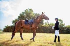 Härlig jockeyflickaställning bredvid hennes häst Royaltyfria Bilder