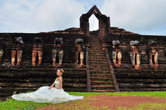 härlig klänning som sitter den thai traditionella kvinnan Royaltyfria Bilder