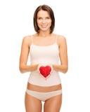 Härlig kvinna i bomullsunderkläder och röd hjärta Royaltyfri Fotografi