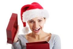 Härlig kvinna i den santa hatten och öppningsgåva. Arkivfoto