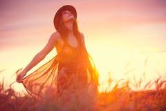 Härlig kvinna i guld- fält på solnedgången Arkivbild