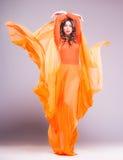 Härlig kvinna i långt orange posera för klänning som är dramatiskt i studion Arkivfoton