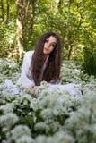 Härlig kvinna i långt vitt klänningsammanträde i en skog Arkivfoton