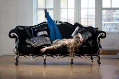 Härlig kvinna i lyxig sofa Arkivbilder