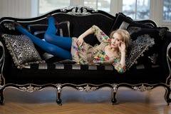 Härlig kvinna i lyxig sofa Arkivfoto