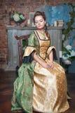 Härlig kvinna i medeltida klänning på stolen Fotografering för Bildbyråer