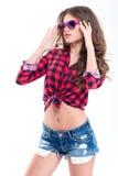Härlig kvinna i rutig skjorta, jeanskortslutningar och rosa solglasögon Fotografering för Bildbyråer