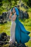 Härlig kvinna med att posera för blåttkappa Arkivbild