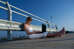 Härlig kvinna med bärbar dator på semester Arkivfoto