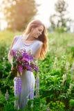 Härlig kvinna med buketten av vildblommor i äng Arkivfoton