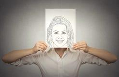 Härlig kvinna med den lyckliga självståenden framme av hennes framsida och att dölja riktiga sinnesrörelser Arkivfoto