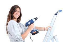 Härlig kvinna med en drillborr på en stege Arkivbilder